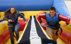 A boy and a teenage girl running hard on a bungee run course in McDonough, GA