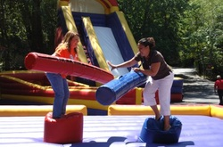 Two adults having fun while standing on top of inflatable joust pods at a fraternity in Atlanta, Georgia