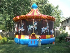 Children playing on a carnival and fair themed inflatable carousel